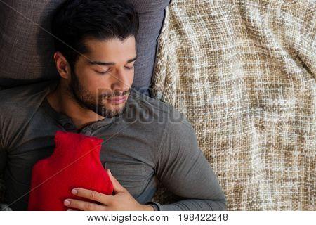 Man sleeping with hot water bag at home