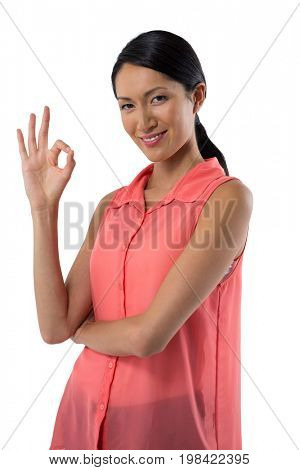 Portrait of smiling woman gesturing okay hand sign against white background