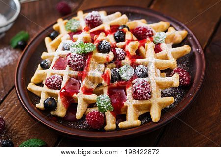 Belgium Waffles With Raspberries And Syrup On A Plate.