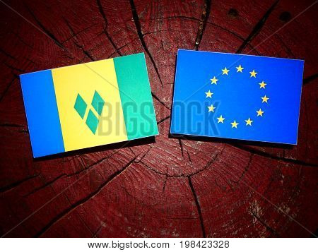 Saint Vincent And The Grenadines Flag With Eu Flag On A Tree Stump Isolated