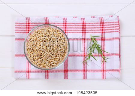bowl of cooked pearl barley on checkered dishtowel