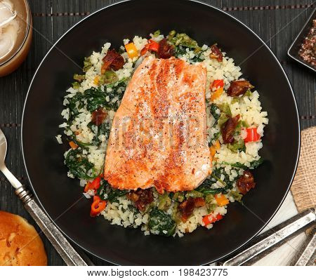 Salmon with Riced Cauliflower and Vegetable Salad at table.