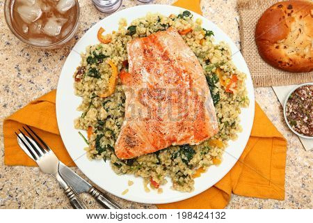 Salmon with Cracked Freekeh Salad at table with spicy salsa verde, iced tea, salsa verde, and an onion roll.