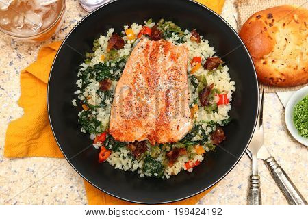 Salmon with Riced Cauliflower and Vegetable Salad at table with Iced Tea and Onion Roll.
