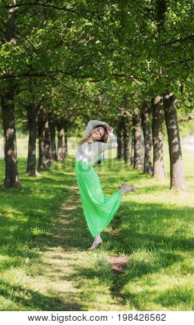 Elegant slender girl on a path in a summer park