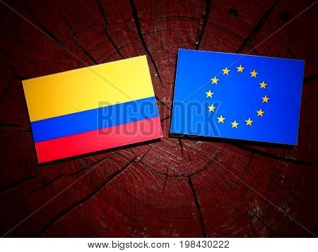 Colombian Flag With Eu Flag On A Tree Stump Isolated