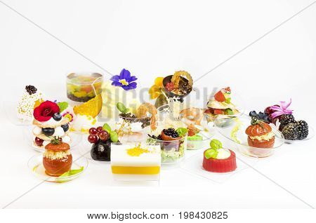 Mini desserts and meat canapes vegetable snacks in plastic cups canapes