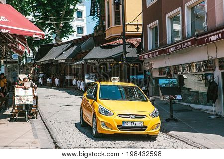 Editorial image of yellow taxi cab in shopping district in Istanbul, Turkey on June 15, 2017.