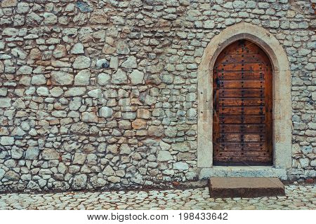 Wooden door with metal rivets in the old stone wall on the street of the ancient city