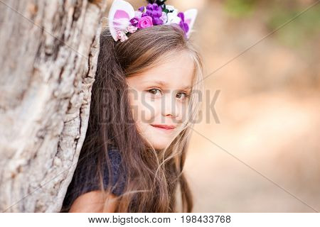 Smiling baby girl 4-5 year old posing outdoors. Looking at camera. Wearing handmade headband. Childhood.