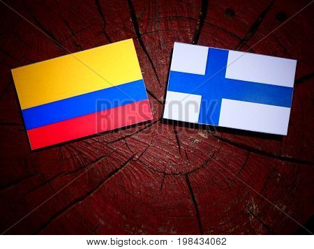 Colombian Flag With Finnish Flag On A Tree Stump Isolated