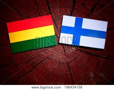 Bolivian Flag With Finnish Flag On A Tree Stump Isolated