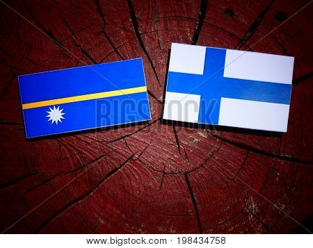 Nauru Flag With Finnish Flag On A Tree Stump Isolated