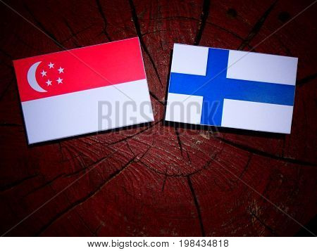 Singaporean Flag With Finnish Flag On A Tree Stump Isolated