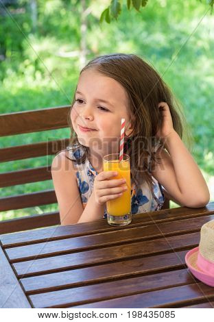 Little happy girl drinks orange juice from a glass in a cafe on a grassy background