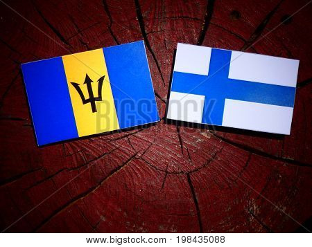 Barbados Flag With Finnish Flag On A Tree Stump Isolated