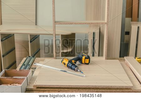 Assembling furniture from chipboard using a cordless screwdriver close up.