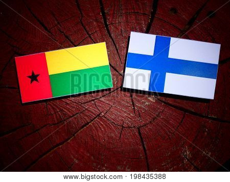 Guinea Bissau Flag With Finnish Flag On A Tree Stump Isolated