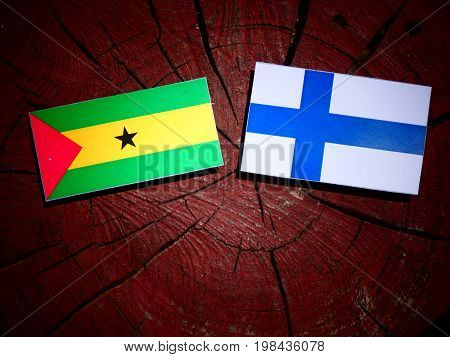 Sao Tome And Principe Flag With Finnish Flag On A Tree Stump Isolated