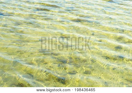 Texture of a yellow water surface. Sandbed.