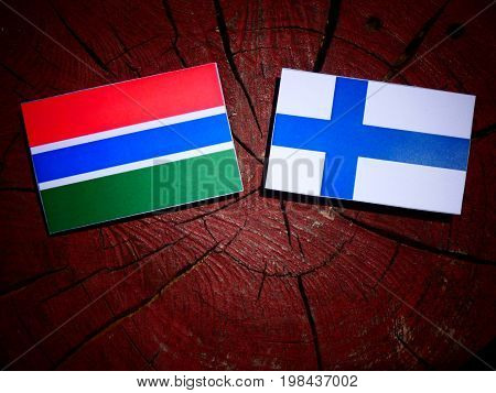 Gambian Flag With Finnish Flag On A Tree Stump Isolated