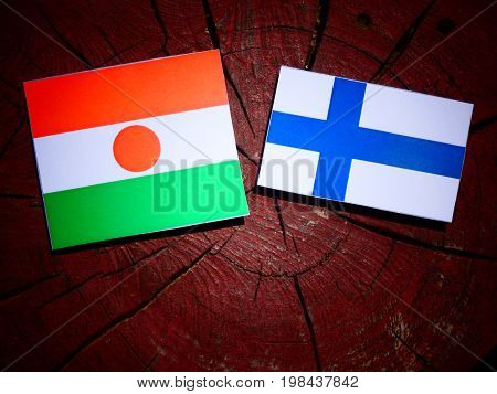 Niger Flag With Finnish Flag On A Tree Stump Isolated