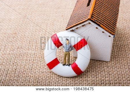 Model House And A Life Preserver With A Man Figure