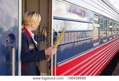 Vyazma, Russia - July 29, 2010: The train conductor gives a signal for the departure