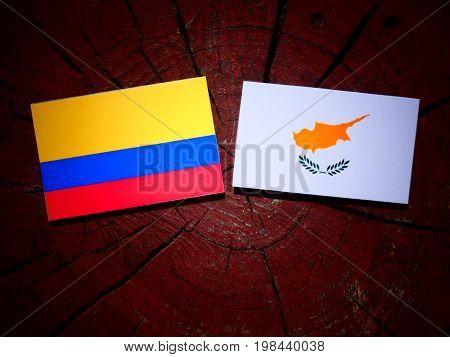 Colombian Flag With Cypriot Flag On A Tree Stump Isolated