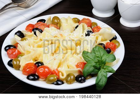 Pasta with olive garlic basil and tomatoes and seasoned with Parmesan cheese.