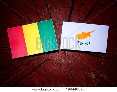 Guinean Flag With Cypriot Flag On A Tree Stump Isolated