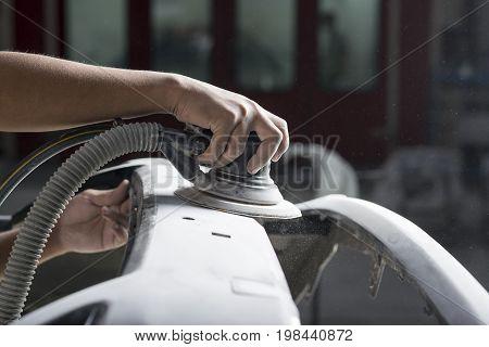 Auto body repair series: Closeup of mechanic sanding car bumper