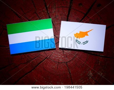 Sierra Leone Flag With Cypriot Flag On A Tree Stump Isolated