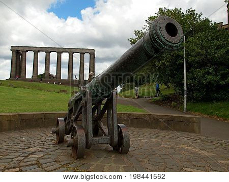 Gun and National Monument of Scotland. Edinburgh, Scotland - July 27, 2017 The historic cannon and the National Monument of Scotland, on Calton Hill in Edinburgh.