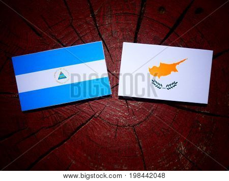 Nicaraguan Flag With Cypriot Flag On A Tree Stump Isolated
