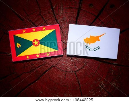 Grenada Flag With Cypriot Flag On A Tree Stump Isolated