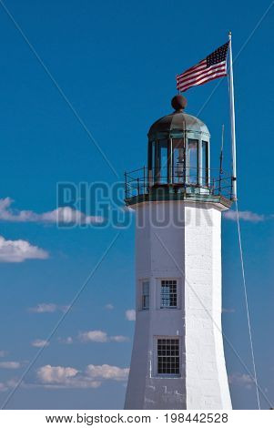 Flag waves over Scituate lighthouse tower in Massachusetts. Scituate Lighthouse is still the oldest complete lighthouse, in the country.