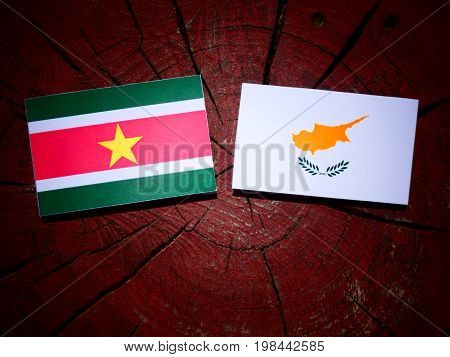 Suriname Flag With Cypriot Flag On A Tree Stump Isolated
