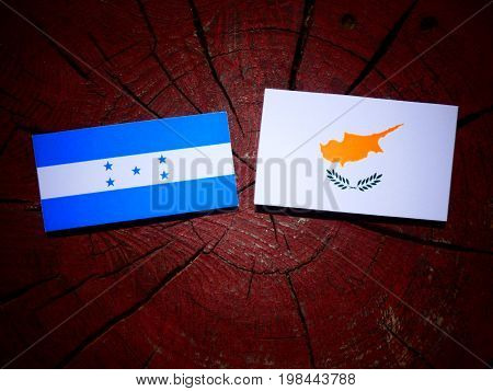 Honduras Flag With Cypriot Flag On A Tree Stump Isolated