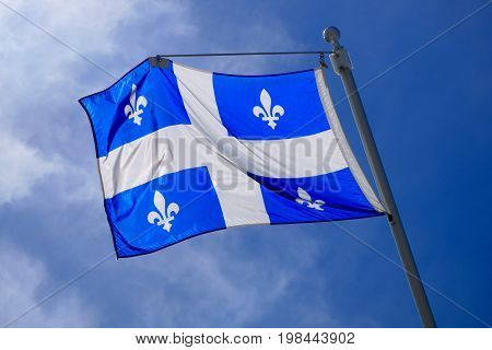 national Quebec flag in Canada fluttering in the wind on blue sky