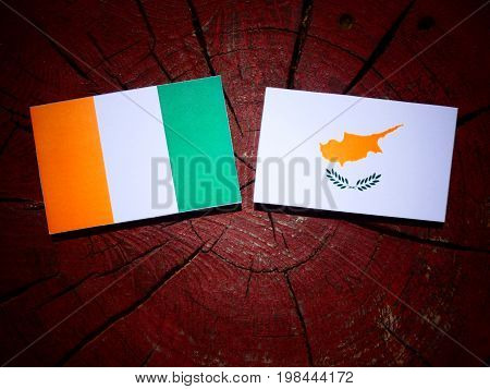 Ivory Coast Flag With Cypriot Flag On A Tree Stump Isolated