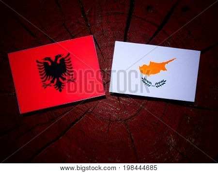 Albanian Flag With Cypriot Flag On A Tree Stump Isolated