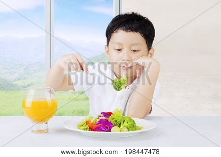 Little boy sitting at home and looks dislike a plate of vegetables salad