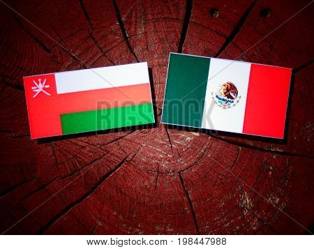 Omani Flag With Mexican Flag On A Tree Stump Isolated