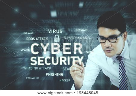 Picture of young businessman wearing glasses while writing a text of cyber security on the virtual screen
