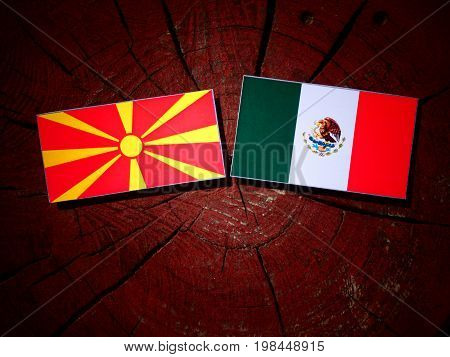 Macedonian Flag With Mexican Flag On A Tree Stump Isolated