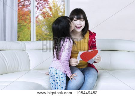 Little girl kiss her mother cheek after giving a greeting card on the sofa at home shot with autumn background on the window