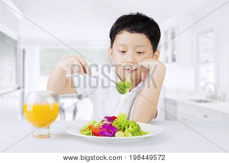 Male child sitting in the kitchen at tasting a plate of vegetables salad shot at home