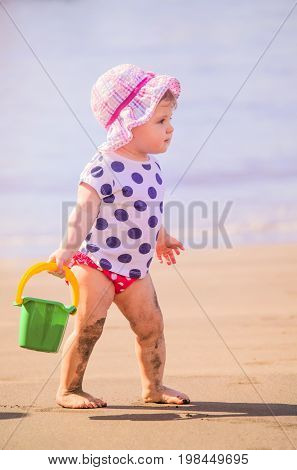 Little girl aged 2 playing on the beach with pail and shovel, Canary Islands