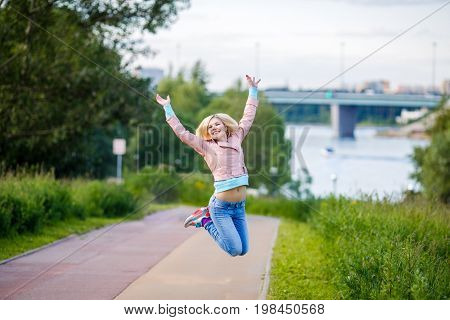 Woman Jumps With Arms Raised